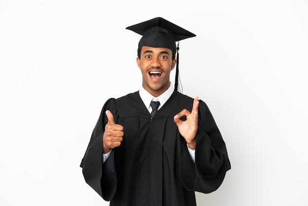 Afroamericano laureato uomo su sfondo bianco isolato che mostra segno ok e pollice in alto gesto
