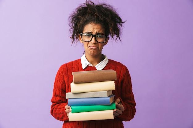 Ragazza arrabbiata afroamericana in uniforme scolastica che tiene mazzo di libri, isolata