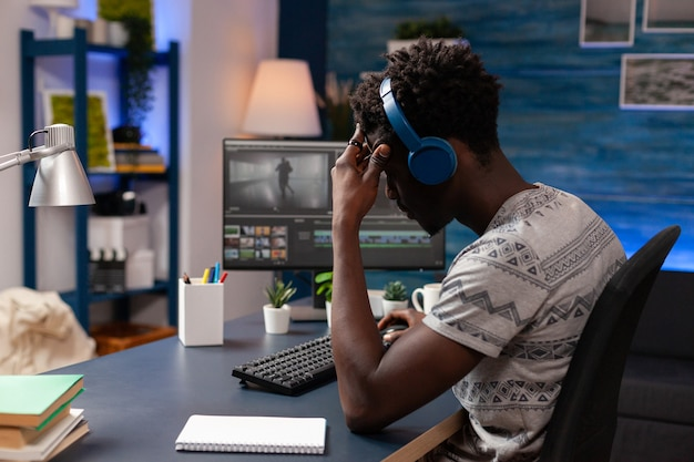 Videomaker afroamericano che ritocca filmati utilizzando un software di post produzione