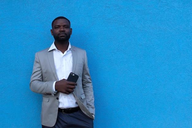 Afroamericano con il telefono contro il muro blu