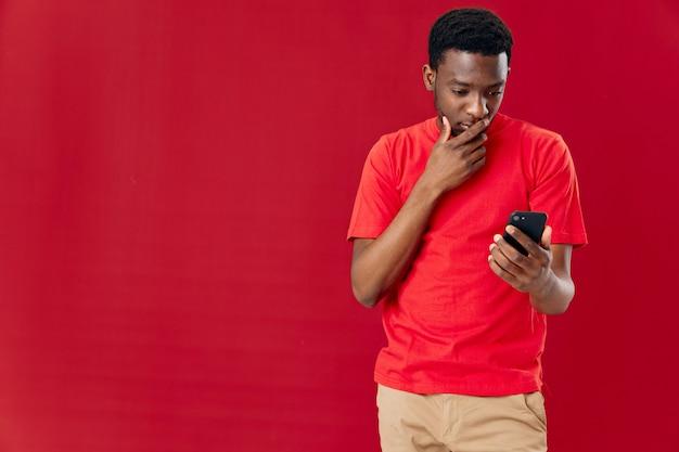 L'afroamericano con un telefono in mano guarda nella forma isolata dello studio del telefono