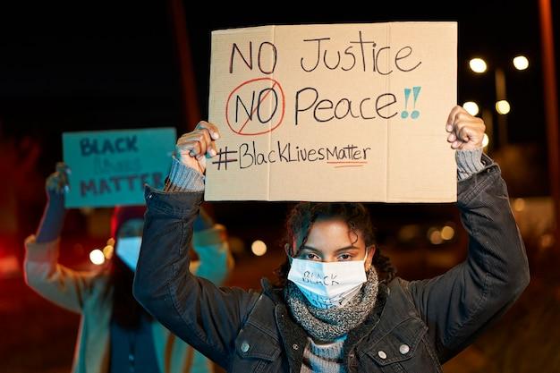 Donna afro-americana che dimostra contro il razzismo, con in mano uno striscione. manifestanti in una città con striscioni in lotta per i propri diritti. la vita nera è importante.