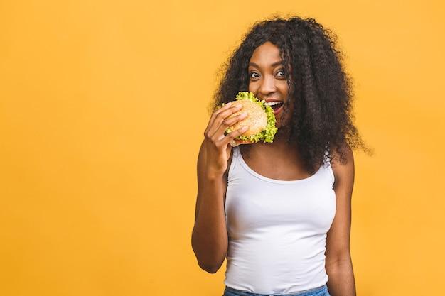Donna afro-americana che mangia hamburger