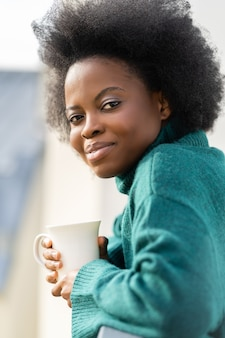 Donna afroamericana che gode di una tazza di tè o di caffè che guarda l'obbiettivo in piedi sul balcone