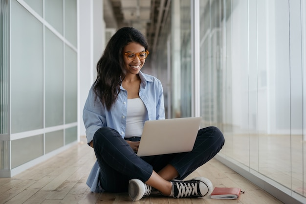 Libero professionista afroamericano donna utilizzando computer portatile, digitando, avendo videochiamata, lavorando da casa