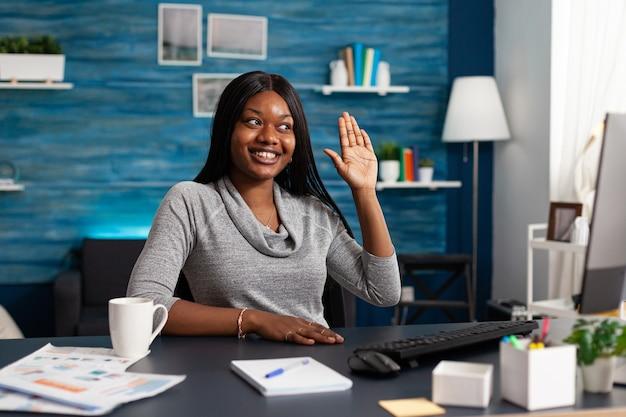 Donna afroamericana saluta il collega universitario discutendo il corso di matematica durante la videochiamata online ...