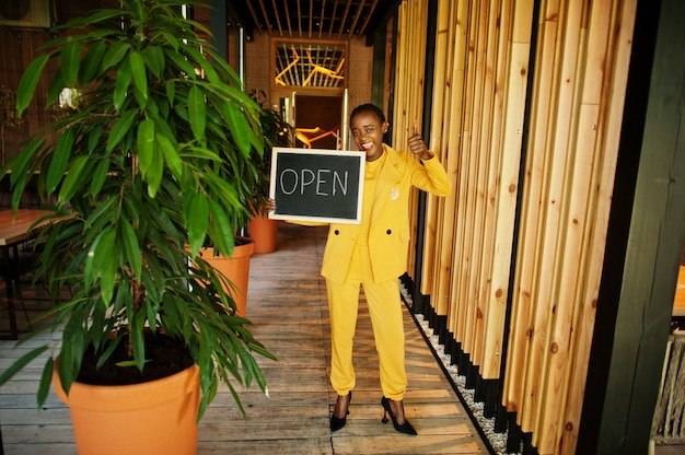 La donna afroamericana tiene aperta il cartello di benvenuto nella moderna caffetteria caffetteria pronta al servizio, ristorante, negozio al dettaglio, proprietario di una piccola impresa.