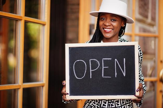 La donna afroamericana tiene aperta il cartello di benvenuto nella moderna caffetteria caffetteria pronta al servizio, ristorante, negozio al dettaglio, proprietario di una piccola impresa. Foto Premium