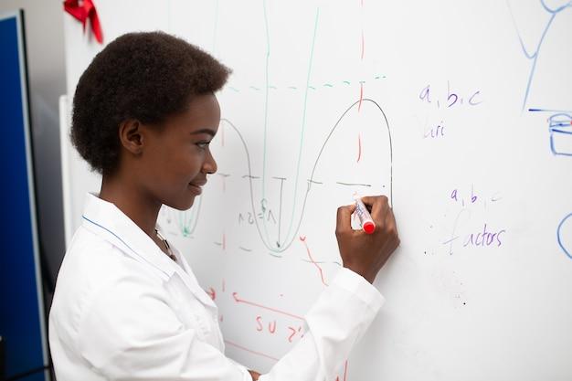 Insegnante di matematica donna afroamericana che scrive sulla lavagna con pennarello