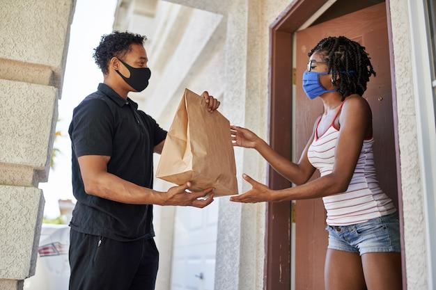Donna afroamericana che apre la porta per ricevere l'ordine da asporto mentre indossa la maschera