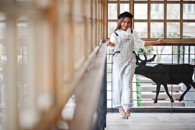La donna afroamericana in tuta e berretto ha posato in terrazzo all'aperto con ghirlanda e cervi delle decorazioni di natale.