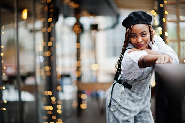 La donna afroamericana in tuta e berretto ha posato in terrazzo all'aperto con la ghirlanda delle decorazioni di natale.