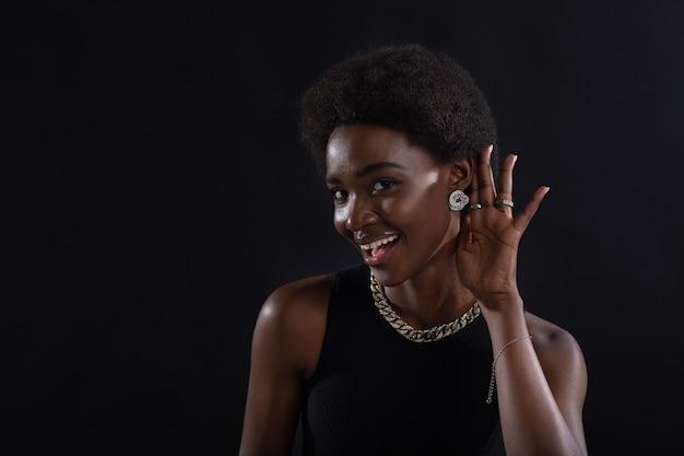 Donna afroamericana che presta attenzione all'ascolto e tiene la mano sull'orecchio voci pettegolezzi segreti e nuovo concetto di informazioni
