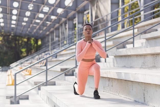 La donna afroamericana esegue esercizi di fitness per la perdita di peso, esegue squat in un abito rosa al mattino nell'aria vicino allo stadio
