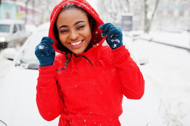 Donna afroamericana in auto pulita felpa con cappuccio rossa dalla neve nel giorno di inverno.