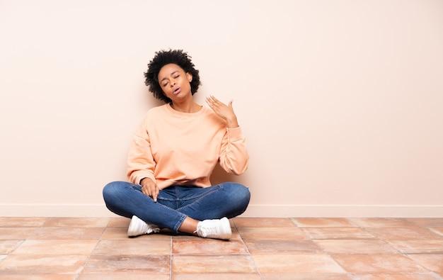 Donna afro-americana seduta sul pavimento con espressione stanca e malata