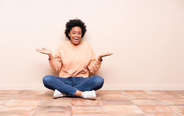 Donna afroamericana che si siede sul pavimento