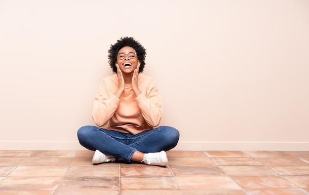 Donna afro-americana seduta sul pavimento