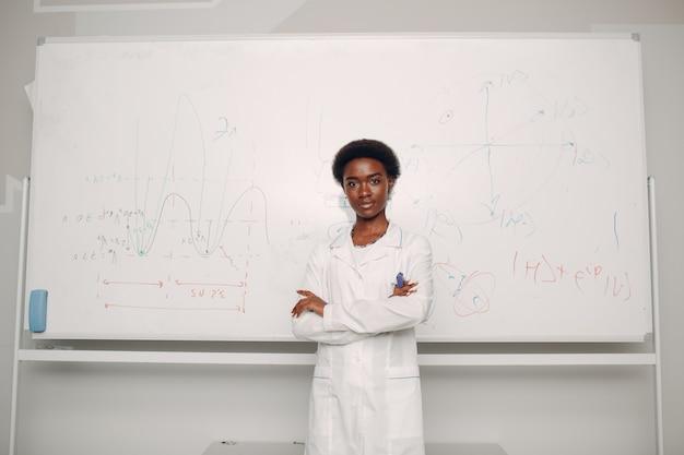 La donna afroamericana sta alla lavagna con la formula e il grafico