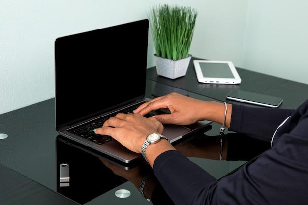 Donna afroamericana che scrive su una tastiera ad un computer portatile moderno