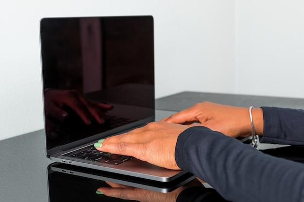 Donna afroamericana che scrive sulla tastiera ad un computer portatile moderno