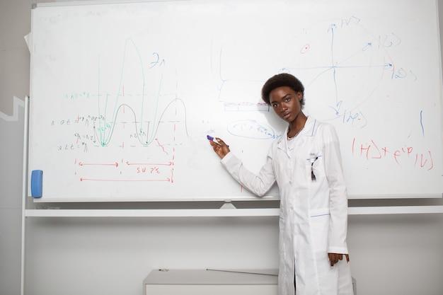 Studente universitario donna afroamericana che scrive sulla lavagna con pennarello