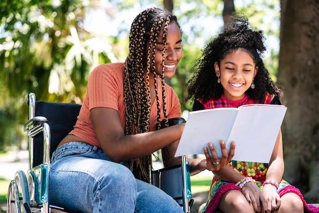 Una donna afroamericana su una sedia a rotelle che gode di una giornata al parco con sua figlia mentre legge un libro insieme