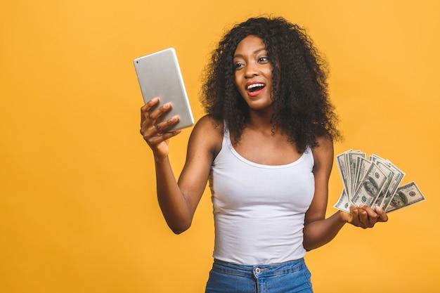 Donna afroamericana con acconciatura afro che tiene un sacco di banconote in dollari di denaro e utilizzo di tablet