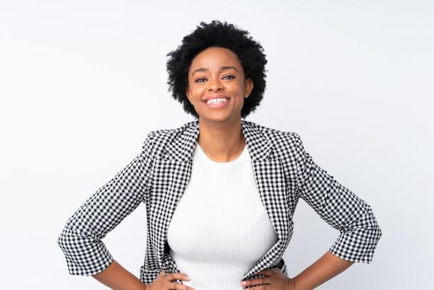 Donna afroamericana con blazer su bianco isolato in posa con le braccia al fianco e sorridente