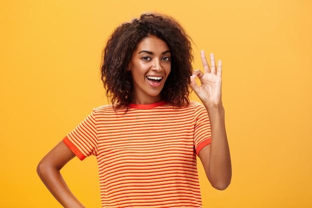 Donna afro-americana con l'acconciatura riccia che mostra gesto giusto e sorridente