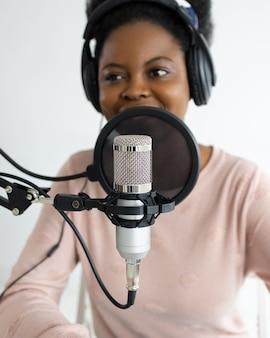 Donna afroamericana con cuffie e microfono che registra un podcast in uno studio di registrazione