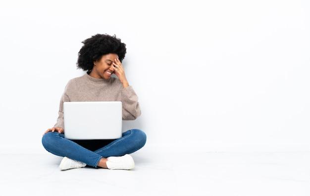 Donna afroamericana con un laptop seduto sul pavimento