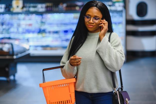 La donna afroamericana con il carrello del carrello nel deposito del supermercato parla sul telefono cellulare.