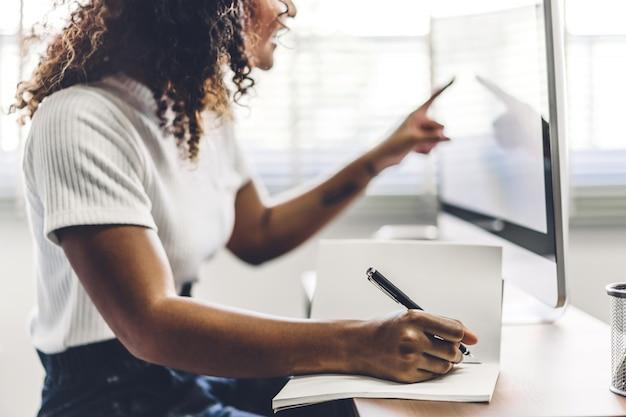 Donna afroamericana che lavora con il computer portatile