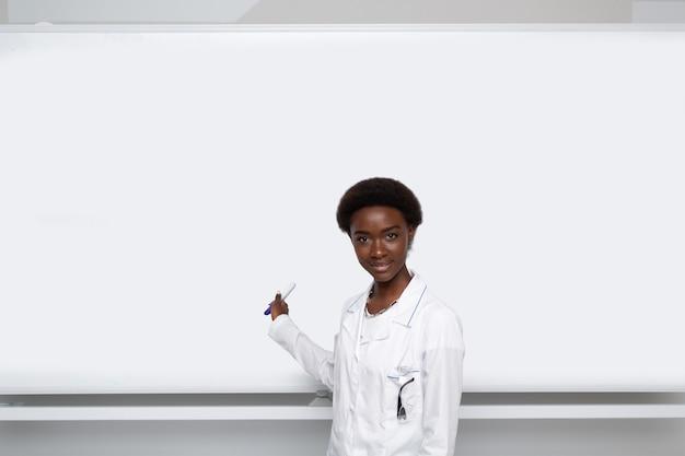 Scrittura della donna afroamericana sulla lavagna vuota del modello con l'indicatore dello spazio della copia.