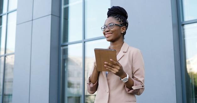 Giovane imprenditrice afroamericana in bicchieri toccando e scorrendo sul dispositivo tablet. messaggio di sms di donna sul computer all'aperto. femmina sicura che utilizza gadget e chat.