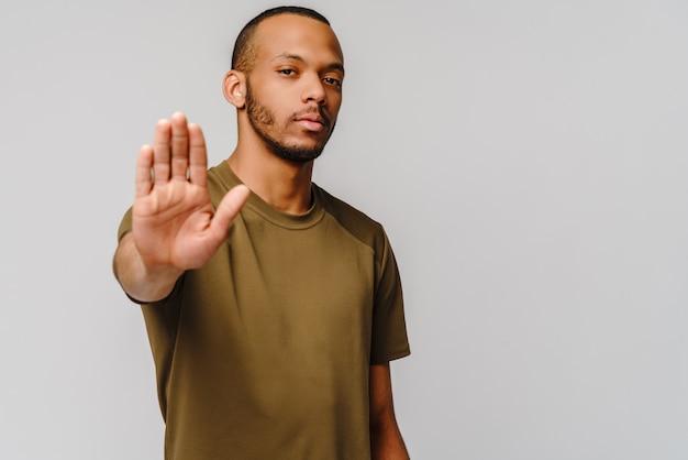 Giovane afroamericano gesticolando stop con la mano sul muro grigio chiaro