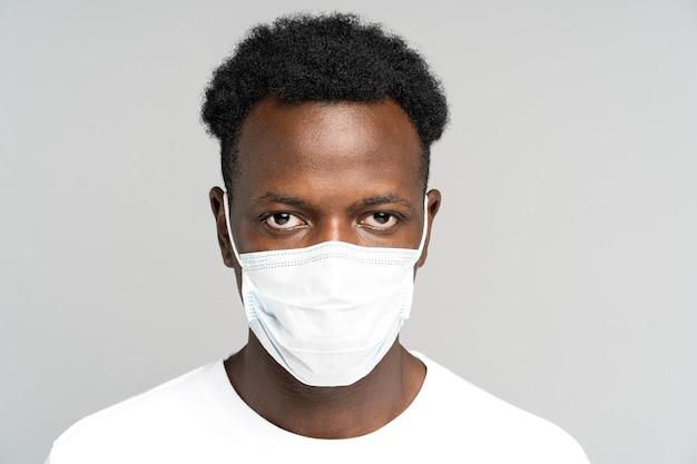 African american giovane uomo che indossa la maschera medica per il viso, guardando la fotocamera, isolata su sfondo grigio
