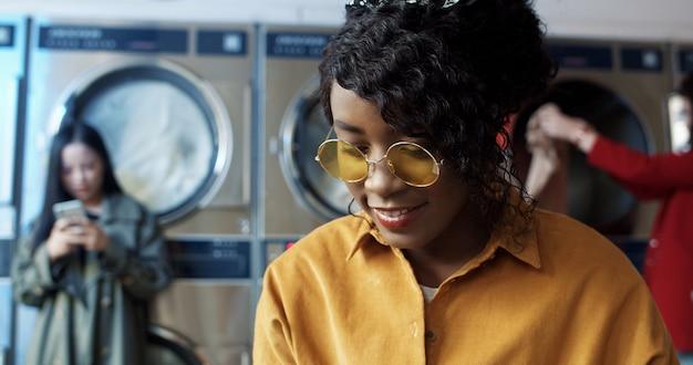 Giovane ragazza graziosa ed alla moda afroamericana in vetri gialli che stanno nella stanza di servizio di lavanderia.