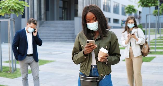 Giovane donna alla moda afroamericana in maschera medica in piedi in strada e messaggio di testo sullo smartphone. femmina toccando all'aperto sul telefono cellulare e tenendo il caffè. pandemia. persone di razza mista.