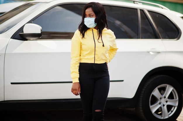 Maschera di protezione d'uso della giovane donna volontaria afroamericana all'aperto contro l'automobile del suv. quarantena del coronavirus e pandemia globale.