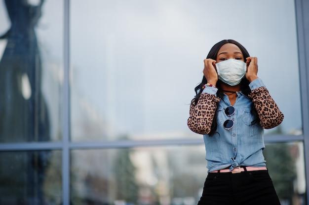 Maschera di protezione d'uso della giovane donna volontaria afroamericana all'aperto. quarantena del coronavirus e pandemia globale.