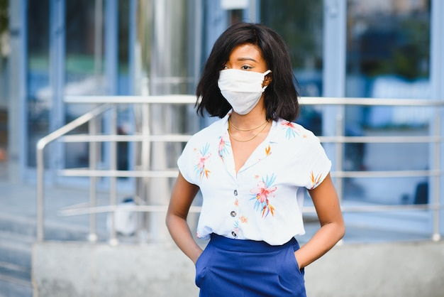 African american giovane volontario donna che indossa la maschera per il viso all'aperto