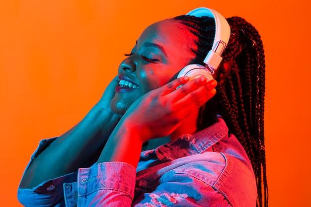 Giovane donna afroamericana che ascolta la musica in linea ballando e cantando con le cuffie, neon