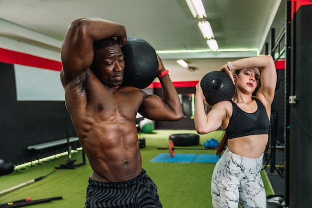 Ragazzo atleta africano e ragazza atleta caucasica in palestra facendo bicipiti della spalla ed esercizi pettorali con una palla di peso in palestra. due culturisti multirazziali