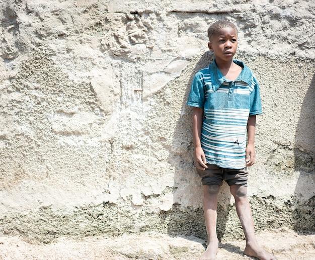 Ritratto di ragazzo nero africano in piedi vicino alla sua povera casa da solo