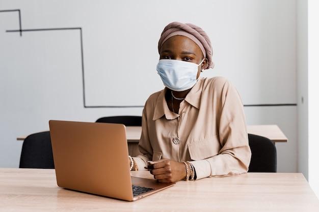 Donna nera africana con il computer portatile. utilizzo del computer per il lavoro in linea. maschera medica per la protezione contro il coronovirus covid-19.