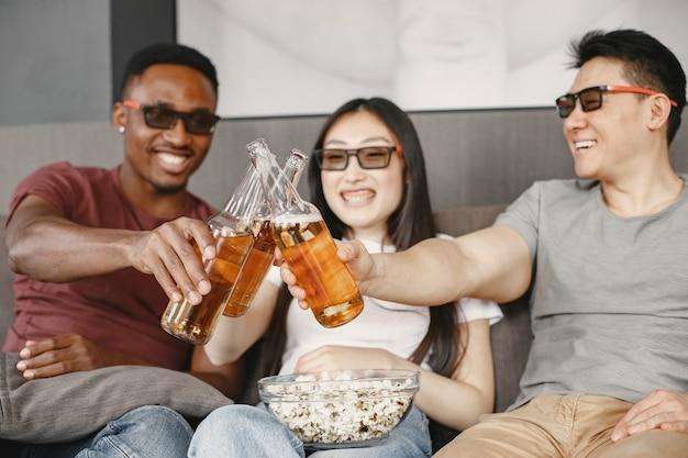 Un ragazzo africano e una coppia asiatica fanno tintinnare una bottiglia con una birra amici che guardano un film mangiano popcorn indossano occhiali per un film in 3d