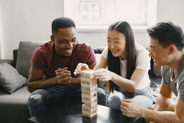Ragazzo africano e coppia asiatica che giocano a jenga gioca al gioco da tavolo nel tempo libero