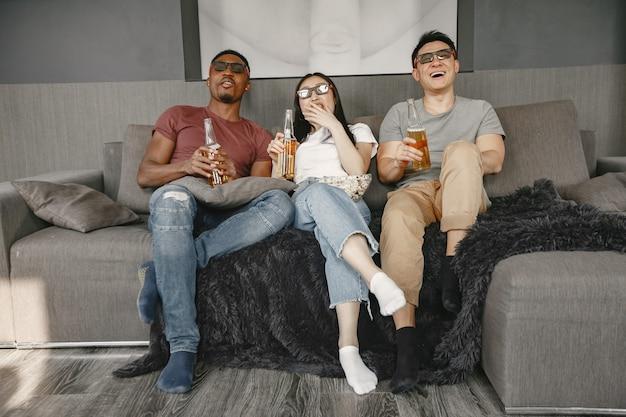 Ragazzo africano e coppia asiatica che guardano film mangiano popcorn e bevono birra indossano occhiali per un film in 3d